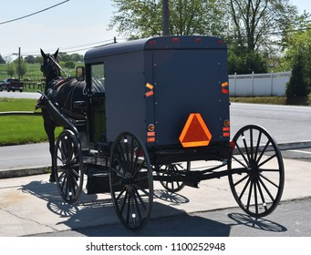 Parked horse drawn Amish buggy at a store.