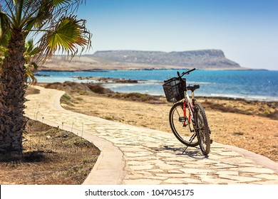 Parked mountain bike on bicycle route against background of the Mediterranean Sea cycling along sea harbour. Bicycle lane bicycle path coastal road clear sunny day. Summer vacation. Cyprus, post card.