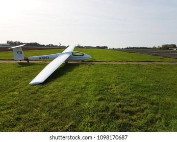 Parked sailplane next to runway.