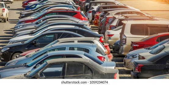parked used cars stand on street during the day