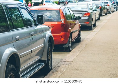parked used cars stand on street parking during the day