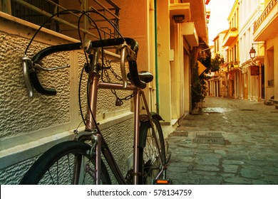 Parked vintage purple old bicycle from the street greek island town panorama, Greece. Close up. Image with sunkissed effect, toned