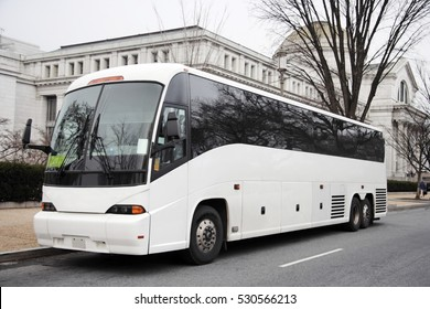 Parked white tour charter sightseeing charter tour bus in urban location. Horizontal.