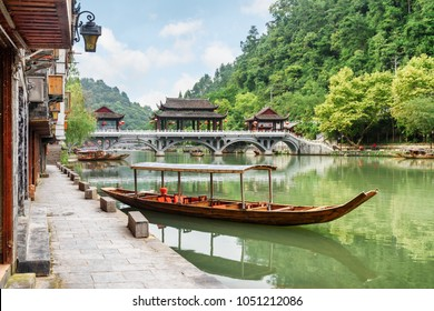 Parked wooden tourist boat on the Tuojiang River and amazing bridge among green woods in Phoenix Ancient Town (Fenghuang County), China. Fenghuang is a popular tourist destination of Asia.