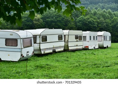 Parking with annuated camper trailers. Row of old-fashioned caravans on a campsite in the Belgian Ardennes.