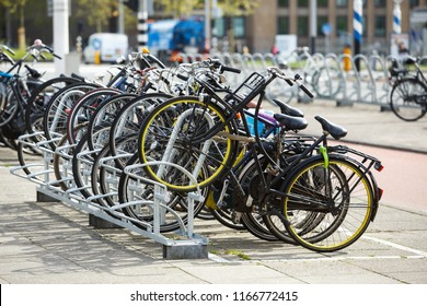 Parking lot with bicycles in the street of big city. Many different bikes parked on metal rack in Amsterdam. Healthy urban transport