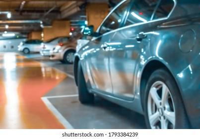 Parking car blurred. Empty road asphalt background in soft focus. Car lot parking space in underground city garage. Interior underground carpark.