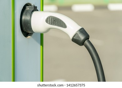 Parking with charging station electric car on a city street. Closeup of car charging cable