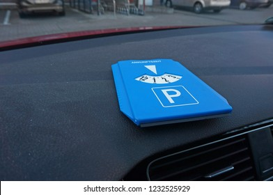 """Parking disc on dashboard. The word on the parking disc means """"arrival time""""."""