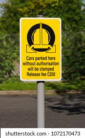 Parking enforcement or wheel clamping sign showing a penalty or release fee for unauthorized vehicles in the UK