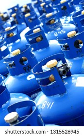 Parking lot full of blue propane gas tanks in an urban environment