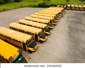 The parking full of school buses waiting for educational season. Row filled with many schoolbus ready to pick up students to school. Drone aerial view from above.