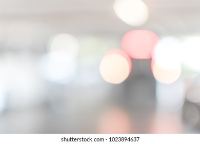 Parking garage blur abstract background with blurry building interior lot space and bright illumination red and front light bokeh of automotive vehicle for car insurance safety concept