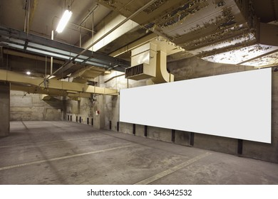 Parking garage underground interior with blank billboard
