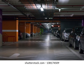 Parking garage, underground interior with a few parked cars