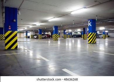 Parking garage, underground interior with a few parked cars. Neon light in bright industrial building.