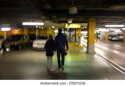 Parking garage, underground interior with a parked cars and people. Intentional motion blur