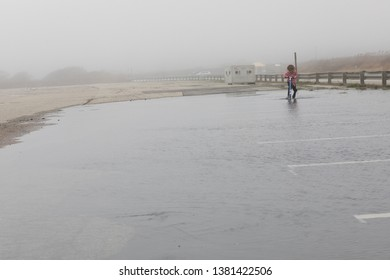 A parking lot is heavily flooded after a hurricane in Newport, RI. A child is playing in the puddle. The climate is wet and foggy after the large coastal storm. Climate change and global warming