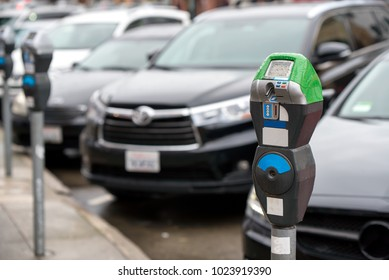 Parking machine with electronic payment in the city streets and a row of cars