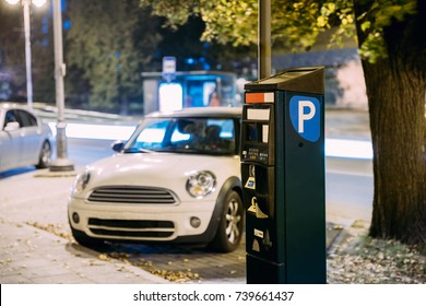 Parking Machine Near Parking At Night. Machine With Electronic Payment That Issues A Permit To Parking Car