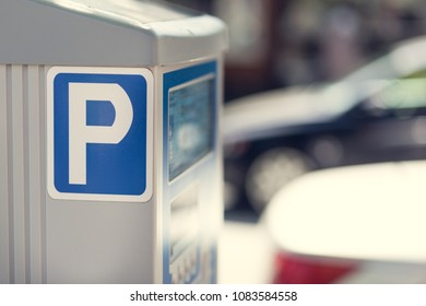 Parking meter and background cars with a depth of field.