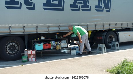 Parking near the city of Koblenz, Germany. March 11.2019: Truck driver washes off his dinner dishes in a parking. Camp kitchen for truckers.