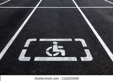 Parking places with handicapped symbol and marking lines on asphalt