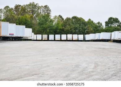 Parking lot of semi-trailers in a gravel parking lot