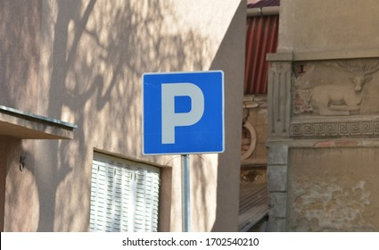 a parking sign on a metal post in the street