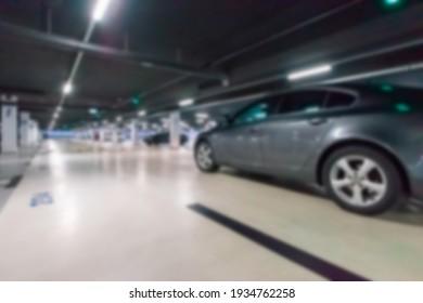 Parking space blurred. Empty road asphalt background in soft focus. Car lot parking space in underground city garage. Hidden underground carpark