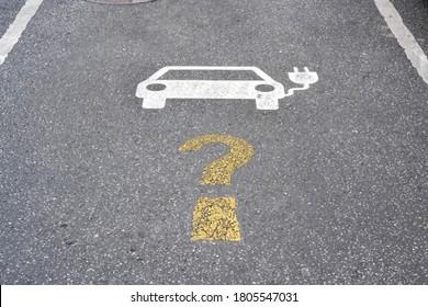 Symbol für die elektrische Ladestation mit Fragezeichen auf Asphalt