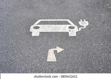 Parksymbol für elektrische Ladestation mit Richtungsschild rechts auf Asphalt