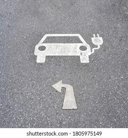 Symbol für elektrische Ladestation des Parks, links auf Asphalt