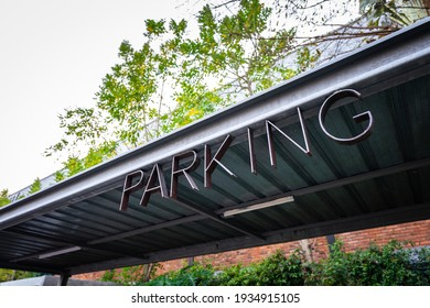 """""""Parking"""" text sign in black metal object on the indoor roof structure, The place of bike or bicycle parking lot in the public park area."""