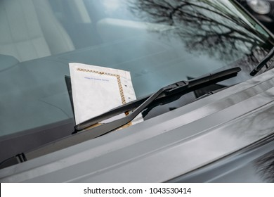 Parking ticket stuck on car windscreen for a penalty or fine.