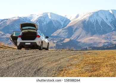 Parking white car in front of mountain