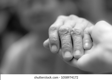 Parkinson and alzheimer female senior elderly patient with caregiver in hospice care. Old woman holding hand with nurse or daughter in black and white.