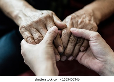 Parkinson and Alzheimer female senior elderly patient with caregiver in hospice care. Doctor hand with stethoscope check up older woman people. Old aging person seeing medical physician in hospital.
