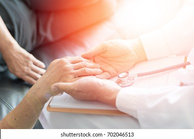 Parkinson and alzheimer female senior elderly patient with caregiver doctor in hospice care.