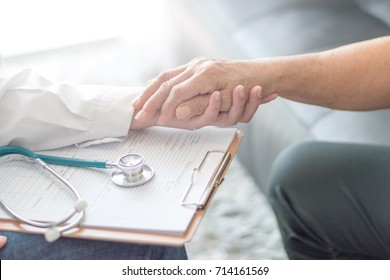 Parkinson and alzheimer female senior elderly patient with caregiver in hospice care. Old woman holding hand with doctor physician.