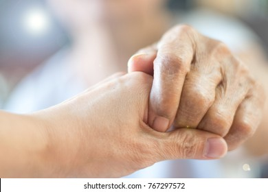 Parkinson and alzheimer female senior elderly patient with caregiver in hospice care. Old woman holding hand with nurse or daughter.