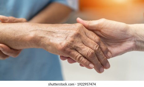 Parkinson disease patient, Alzheimer elderly senior, Arthritis person's hand in support of nursing family caregiver care for disability awareness day, National care givers month, aging society concept