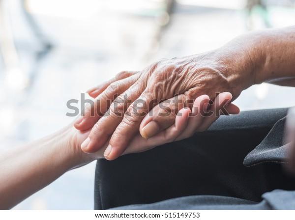 Parkinson-Patient, Alzheimer ältere Alzheimer, Arthritis Person Hand zur Unterstützung der Pflege der Familie Pflege für Behindertenbewusstsein Tag, Nationale Pflegekräfte Monat, Alterung Gesellschaft Konzept