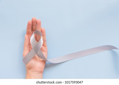 Parkinson's disease awareness or brain cancer grey bow or silver ribbon in woman or female hand over blue background with copy space for text, logo, wordings decoration, health medical concept