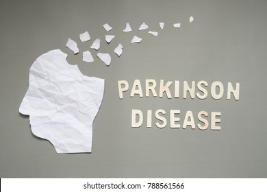 Parkinson's disease concept presented by human head made form white crumpled paper torn on gray background. Creative idea for mental health and neurological disorders.