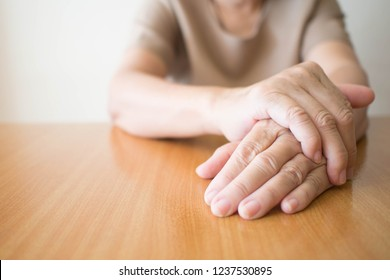 Parkinson's disease symptoms. Close up of tremor (shaking) hands of Middle-aged women patient on wooden table. Mental health and neurological disorders concept. Copy space.