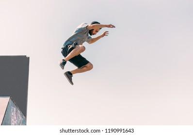 Parkour man exercising parkour jumping below sky