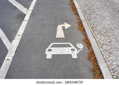 Parksymbol für Elektroauto Ladestation mit Wegweiser nach rechts auf Asphalt