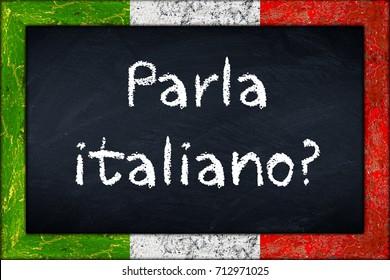 Parla italiano (translation: do you speak italian) language education concept on chalkboard blackboard with wooden italy flag frame