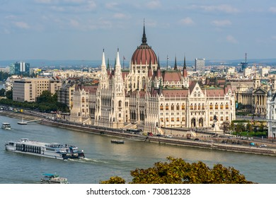 Parliament and boats Budapest. Budapest, Hungary - September 26, 2017: Parliament in Budapest by the Danube river from above. Canal boats and cruise ships with tourist. People all around the building.